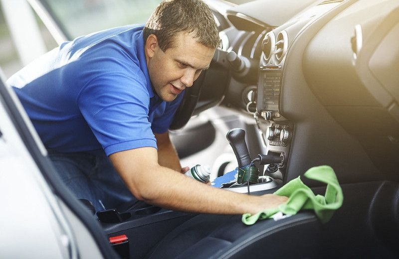 A man cleaning the interior of a car - Sherman Chevrolet in Sherman, TX